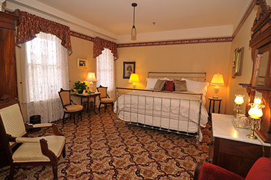 hotel room with king bed two windows with curtains chairs tables and lamps