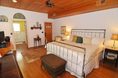 cottage bedroom with iron bed white comforter harwood floors with table dresser and entrance to bathroom