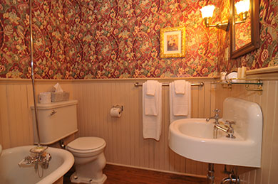 hotel bathroom tub sink toilet with floral wallpaper mirror and lights on wall