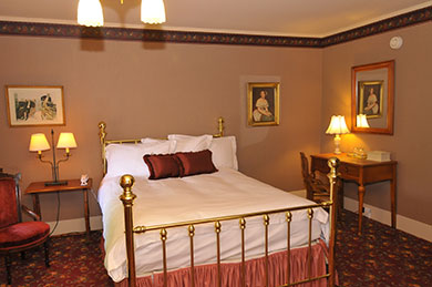 hotel room with queen bed that has brass bars surrounded by two tables lamps and victorian theme pictures on wall