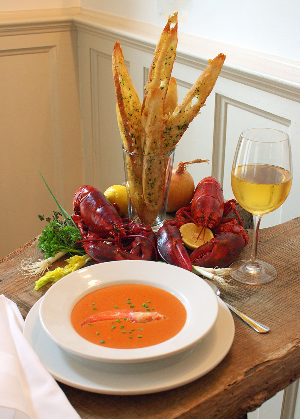lobster bisque in white bowl set on wooden table with glass of white wine bread in glass and lobsters