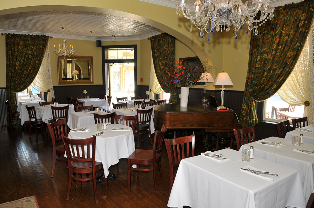 restaurant dining room with white tableclothed tables and wooden chairs piano wooden floors and chandeliers