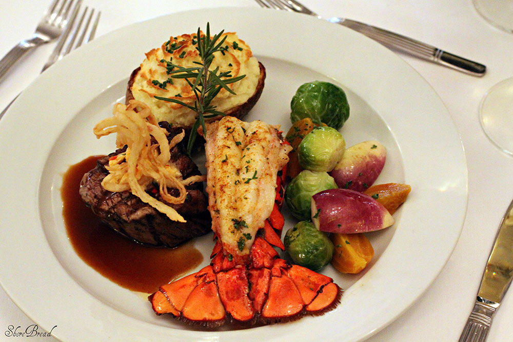 surf and turf steak lobster tail potato vegetables on dining table with silverware