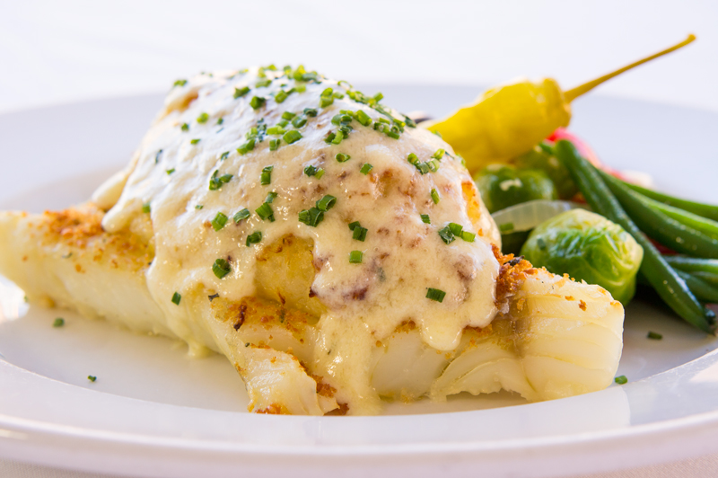 Fish entree with cream sauce on white plate on white tablecloth