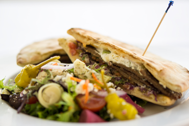 Gyro and salad on white plate on white tablecloth