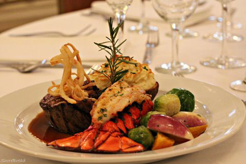 surf and turf steak lobster vegetables on white plate set on white table cloth with glasses and silverware