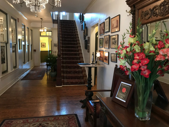 hotel foyer with stairway flowers and table